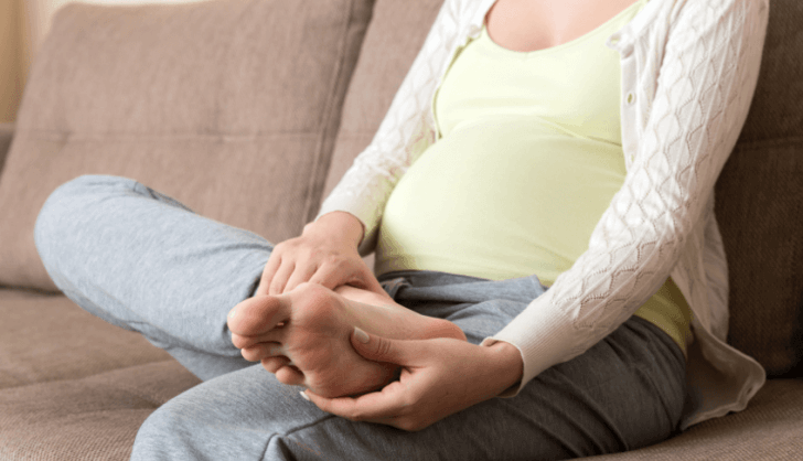 Pregnant woman sitting on the couch holding her foot in pain